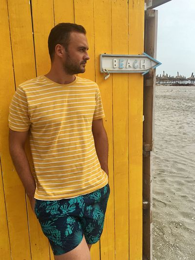 Young man looking away while standing against yellow wall