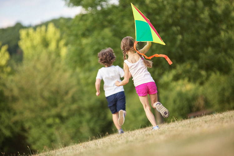 Rear view of friends with kite running on field