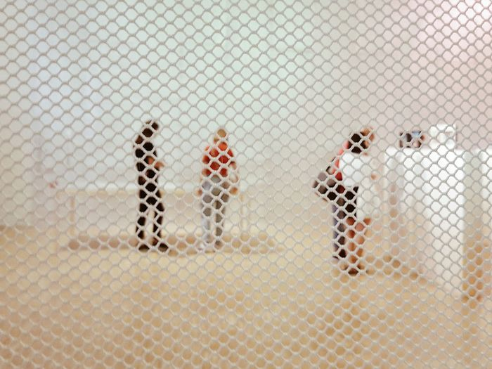 Close-up of figurine people seen through fence