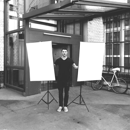 Full Length Of Man Holding Whiteboards In Courtyard
