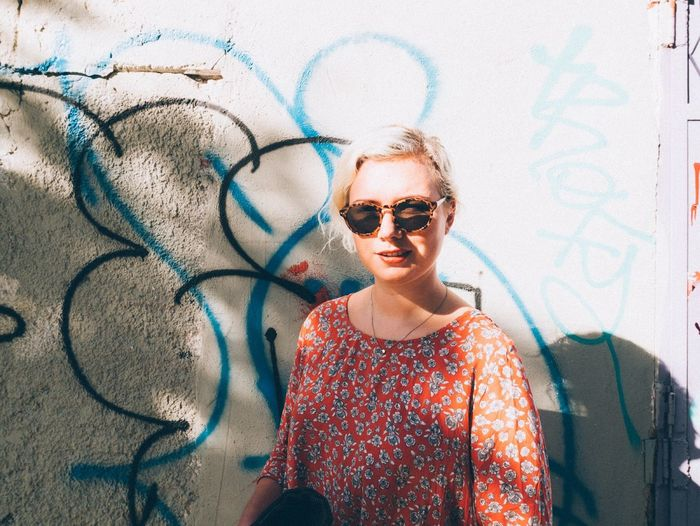 Portrait of woman standing against graffiti