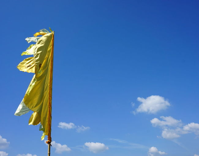 A yellow flag blowing in the wind Art And Craft Belief Blue Cloud - Sky Copy Space Day Flag Low Angle View Nature No People Outdoors Religion Sky Spirituality Sunlight Textile Yellow Yellow Color Yellow Flag