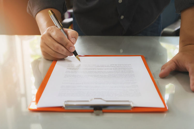 Midsection of businessman reading document on desk in office