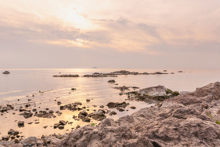 Bright and warm day Water Sky Horizon Horizon Over Water Beauty In Nature Rock Solid Rock - Object Sunset Tranquility Cloud - Sky Nature Land Idyllic Lake Shore Rock Pink Color Pastel Warm Clothing