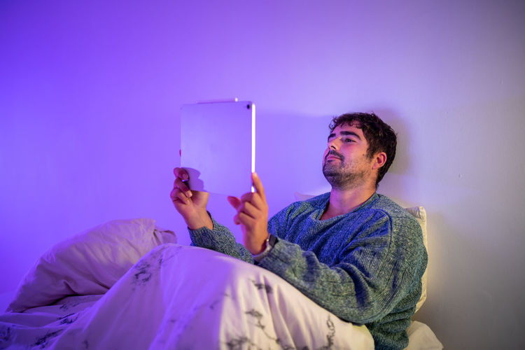 Man using digital tablet sitting on bed against wall at home