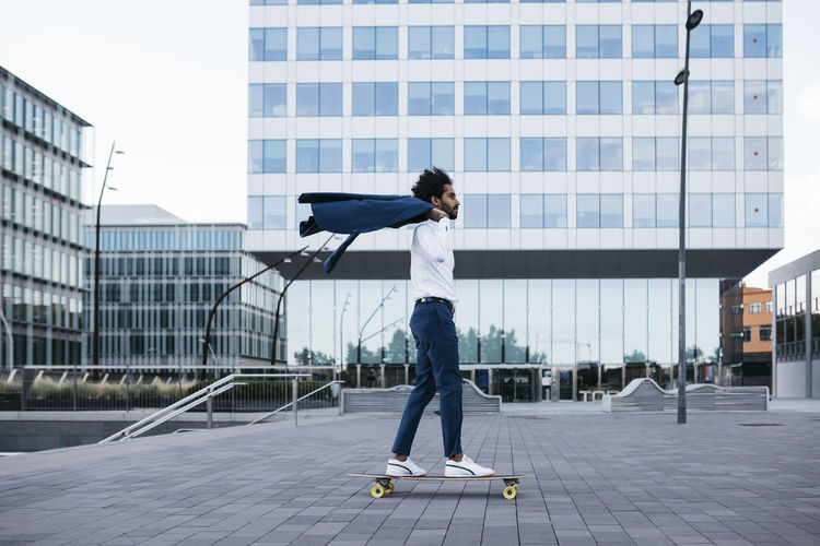 Full length of woman with skateboard standing on street