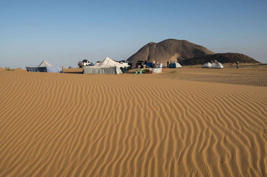 Tourist camp in the Sahara desert with amazing dune in the foreground Tent Camping Sahara Desert Sand Dune Rock Pattern, Texture, Shape And Form Tourist Destination Tourism Sand Scenics - Nature Land Landscape Desert Beauty In Nature Sky Tranquil Scene Clear Sky Tranquility Nature Arid Climate Environment No People Climate Day Built Structure Mountain Non-urban Scene Architecture Atmospheric