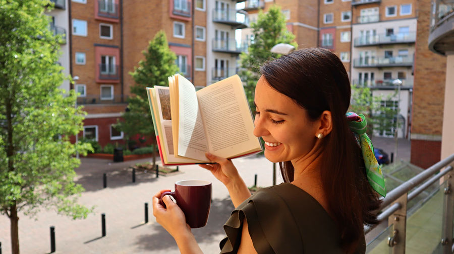 Smiling young woman holding coffee cup and book