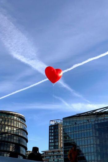 Low angle view of heart shape red balloon against sky in city