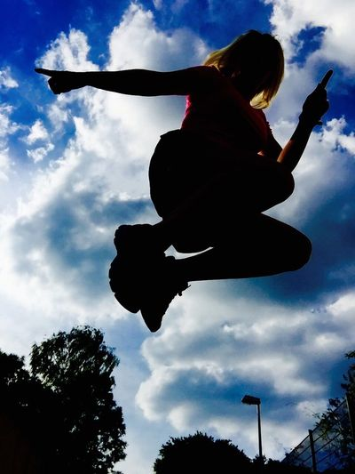 Low angle view of silhouette boy jumping against sky