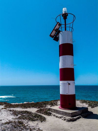 Lighthouse By Sea Against Clear Blue Sky