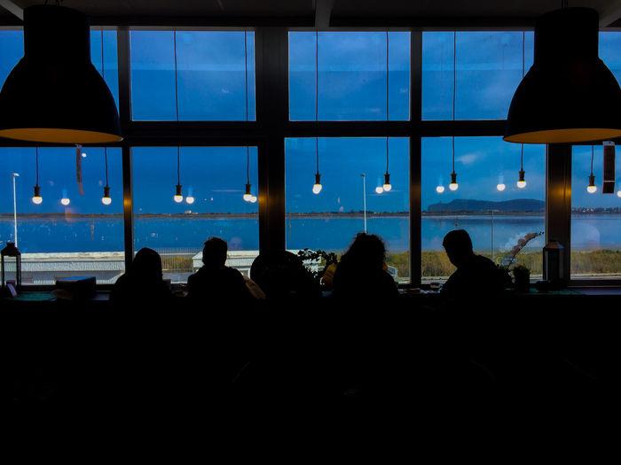 Silhouette people sitting in glass window