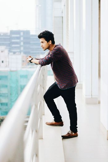 Side view of handsome young man standing at building balcony