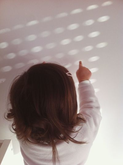 Rear view of girl touching sunlight pattern on white wall