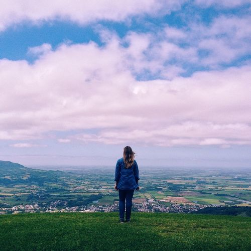 Woman on landscape against cloudy sky
