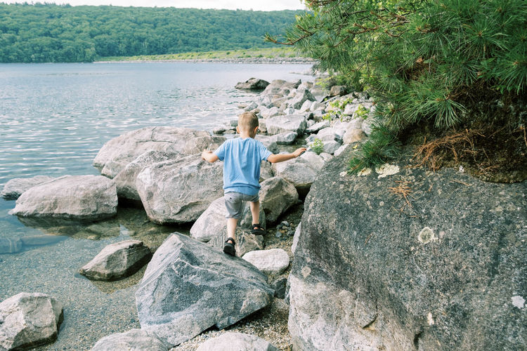 Rear view of man sitting on rock by river