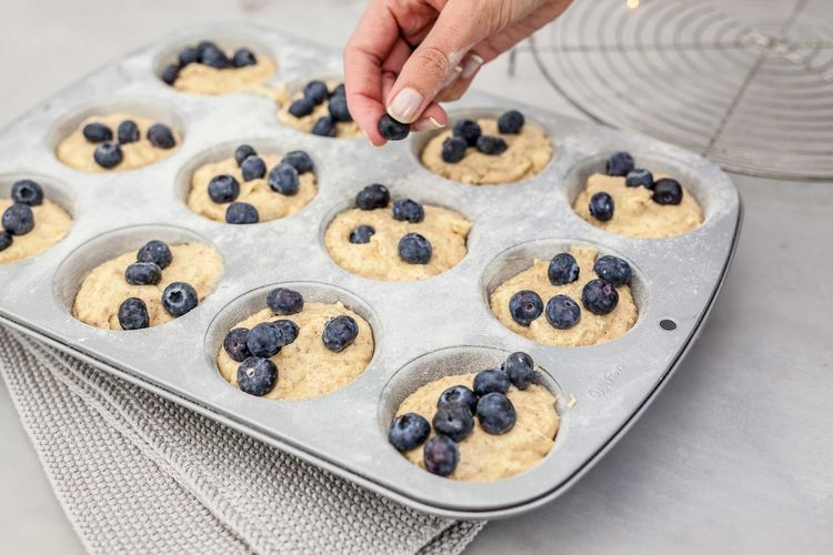 Cropped hand of woman preparing cookies in baking sheet