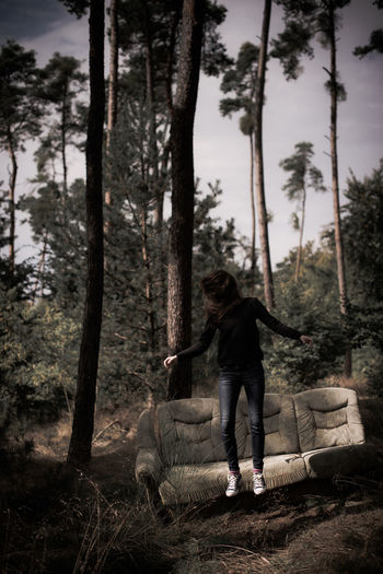 Woman jumping by sofa in forest