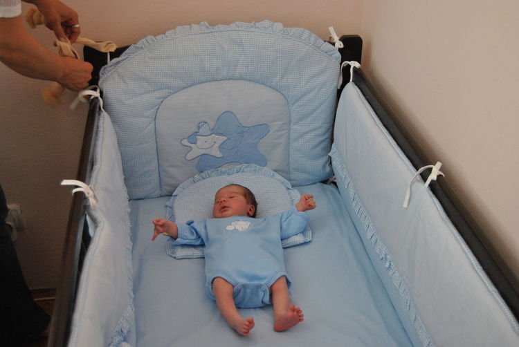 High angle view of child lying in crib