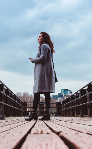 Surface level view of woman standing on footbridge against cloudy sky