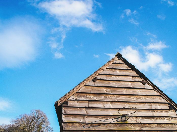 A Wooden Building with a Basketball Hoop Blue Sky Cloud - Sky Architecture Building Exterior No People Outdoors Day Village Wales Britain Triangle Winter Clouds And Sky Trees Sport Exercise Equipment Yard Garden Wood