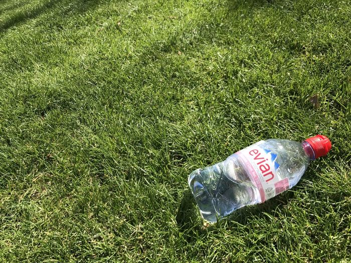 Evian Water Bottle on the grass Bottle Container Day Environment Evian Field Grass Green Color Growth High Angle View Land Nature No People Outdoors Plant Plastic Bag Text Western Script