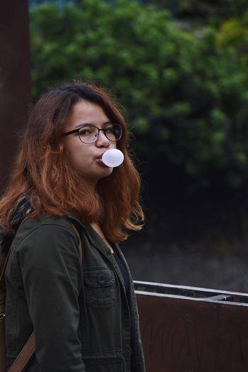 Portrait Of Young Woman Blowing Bubble Gum