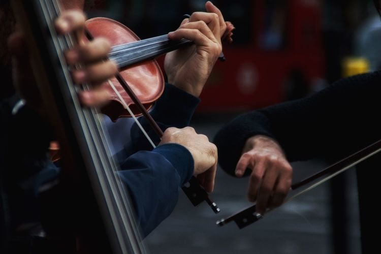 Cropped image of men playing violins on street
