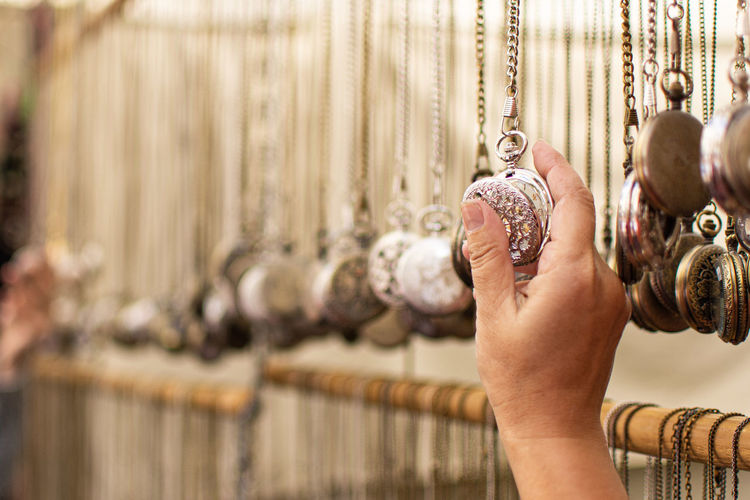 Cropped hand of person holding pocket watch at store