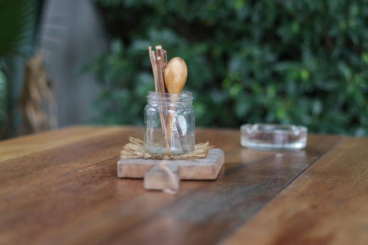 Close-Up Of Stick With Spoon In Jar On Table