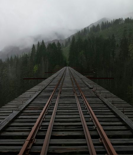 Railway bridge leading towards mountain during foggy weather