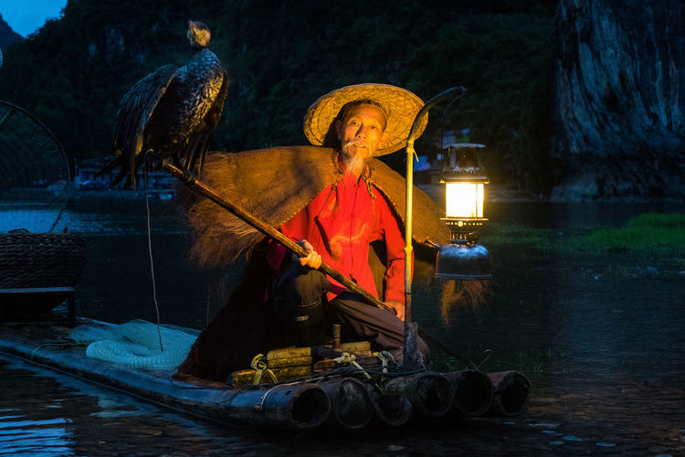 Portrait Of Mature Fisherman With Cormorant By Illuminated Oil Lantern On Wooden Raft In River