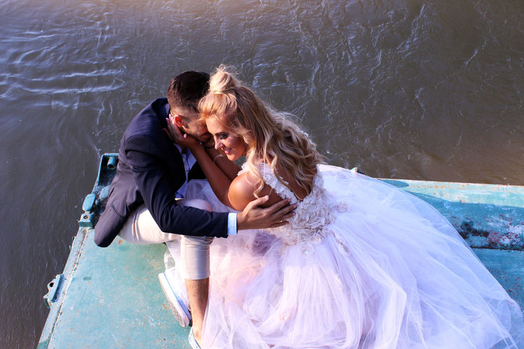 High angle view of smiling bride and groom romancing on pier over lake