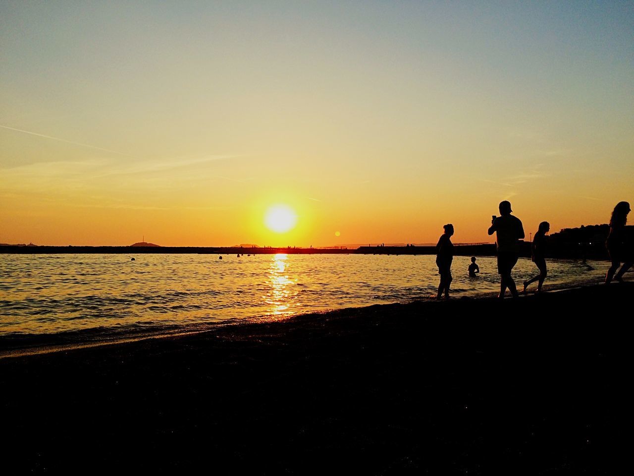 sunset, silhouette, beauty in nature, nature, beach, real people, scenics, orange color, leisure activity, sky, sea, togetherness, sun, lifestyles, tranquil scene, vacations, outdoors, water, men, tranquility, women, sand, full length, horizon over water, friendship, mammal, people
