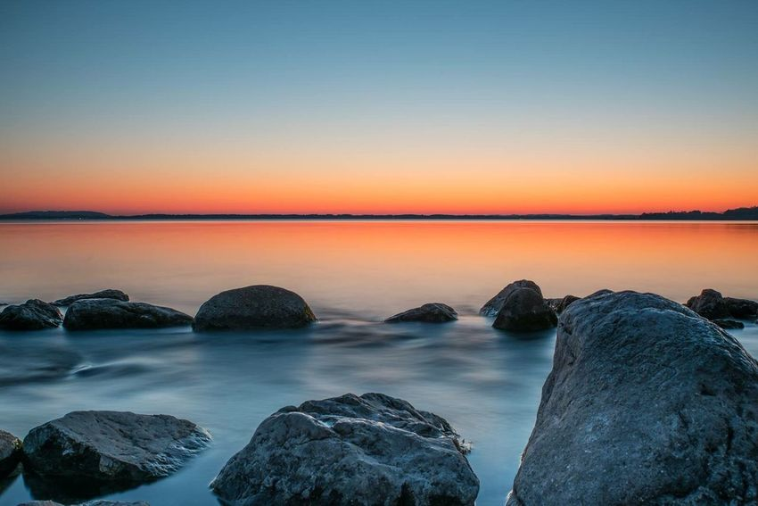 EyeEm Selects Sea Sunset Beauty In Nature Nature Scenics Horizon Over Water Sky Clear Sky Tranquil Scene Tranquility Beach Water Outdoors No People Wave Pebble Beach Day Astronomy