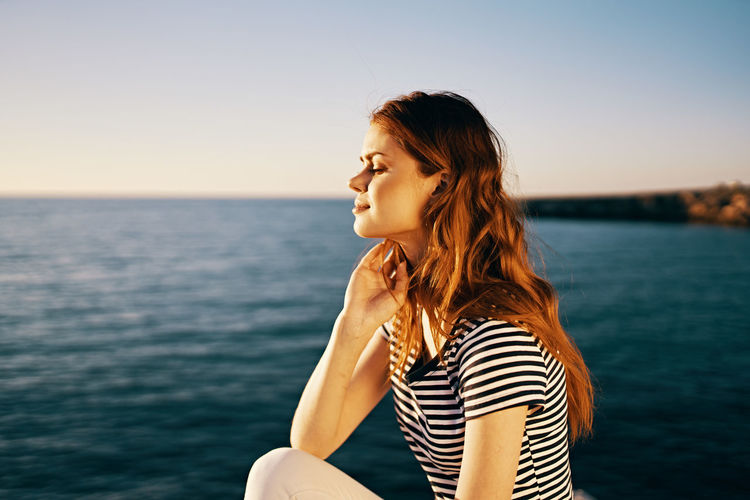 Side view of young woman against sea against sky