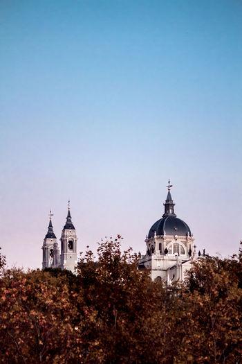 Church by building against clear sky