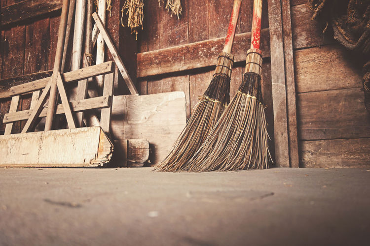 Old brooms placed against a wall with other cleaning stuff. Antique Classic Home Household Housekeeping Housework Hygiene Retro Abstract Aged Broom Broomstick Brush Clean Cleanup Dirt Dust Floor Handmade Hipster House Housecleaning Lifestyles Tidy Vintage