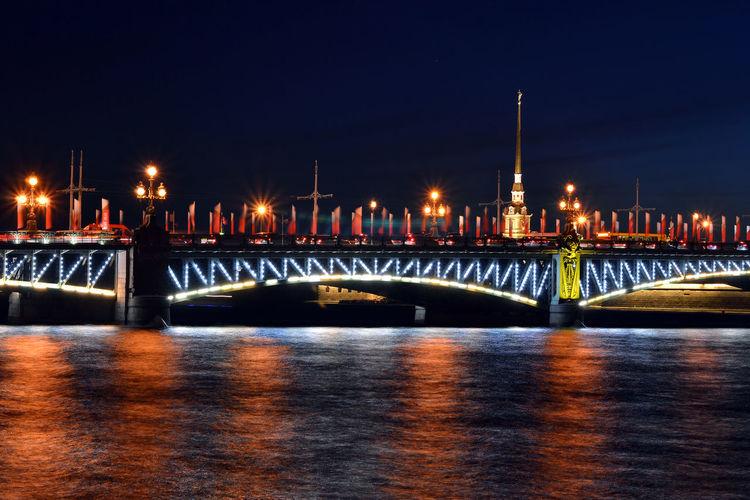 Illuminated Trinity Bridge Over Neva River Against Sky At Night