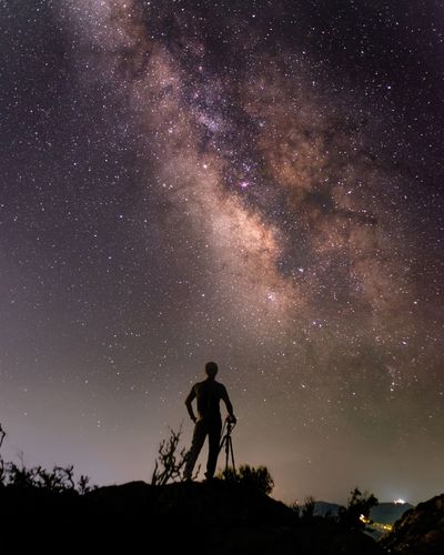 Silhouette Photographer Standing On Field Against Starry Sky At Night