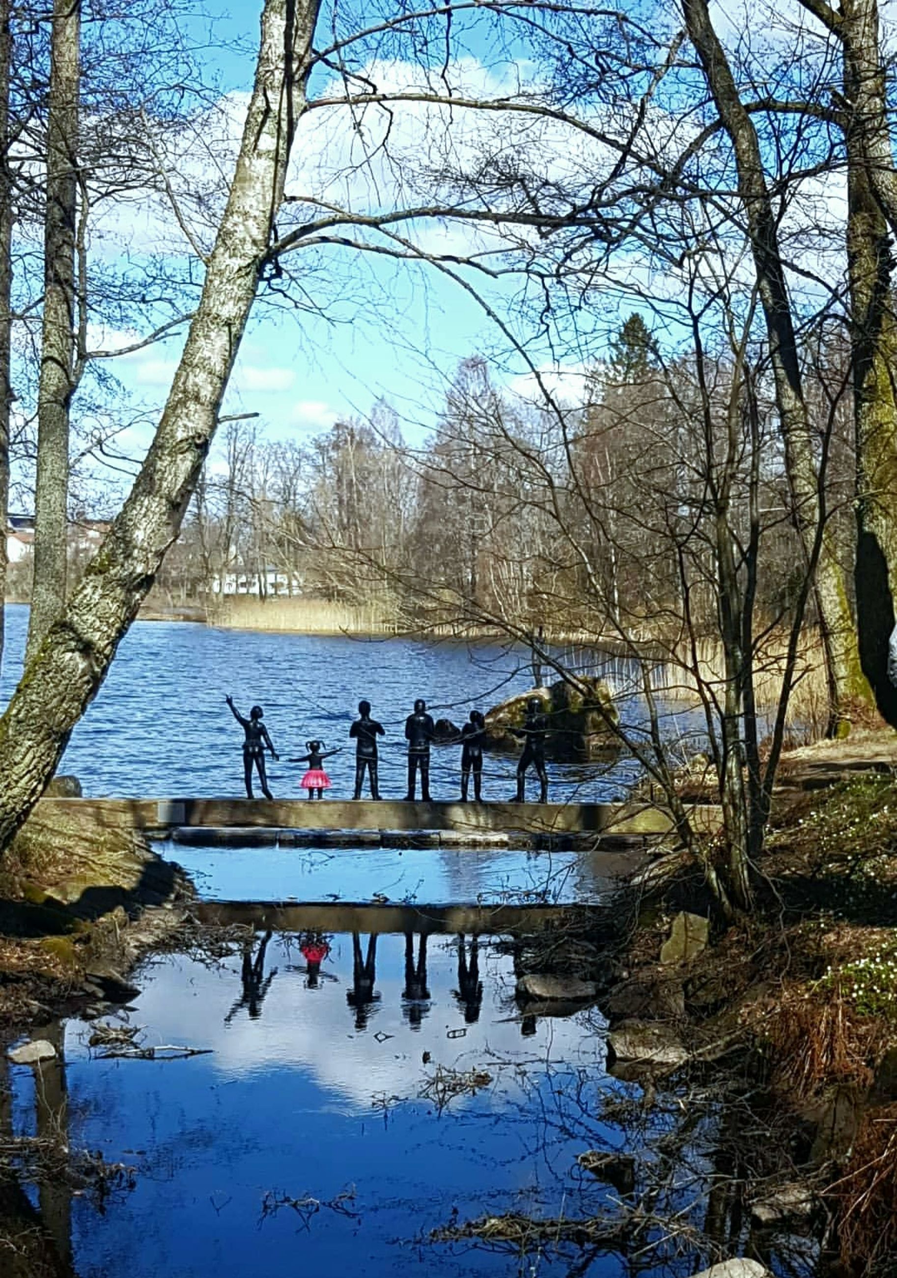 water, group of people, tree, real people, reflection, nature, men, plant, lake, day, bare tree, sky, leisure activity, lifestyles, people, branch, tree trunk, trunk, outdoors