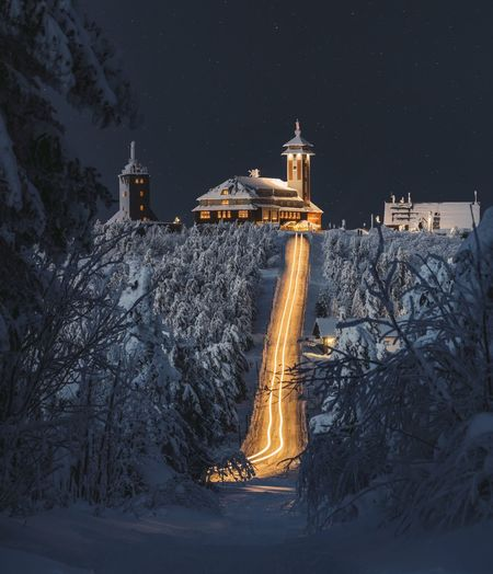 Illuminated building covered with snow at night