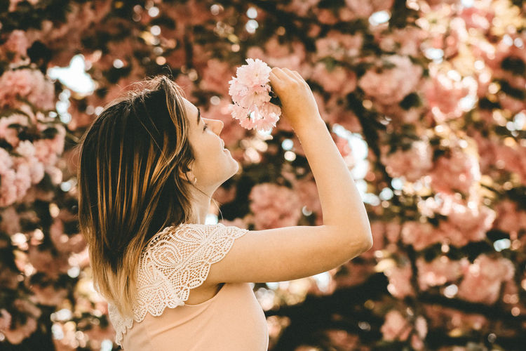 Side view of woman holding flower against tree