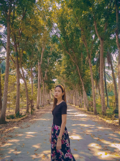 Young woman standing on road amidst trees in forest
