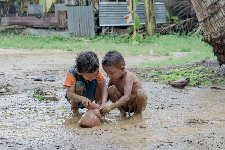 Rear view of shirtless boy on mud