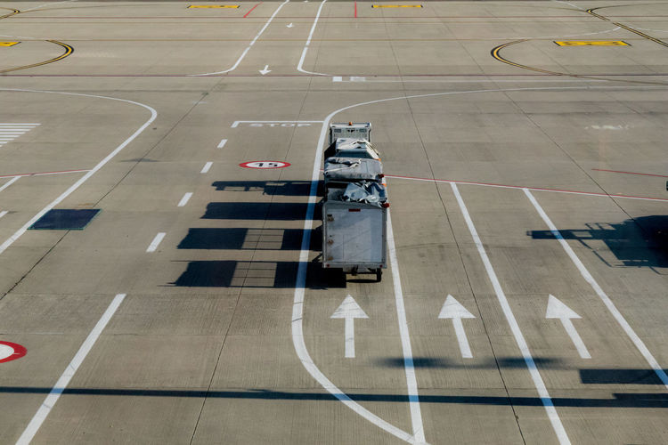 High Angle View Of Luggage Carts By Arrow Sign On Runway