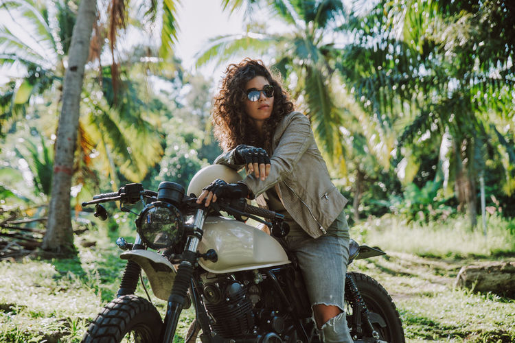 Young woman with motorcycle against trees