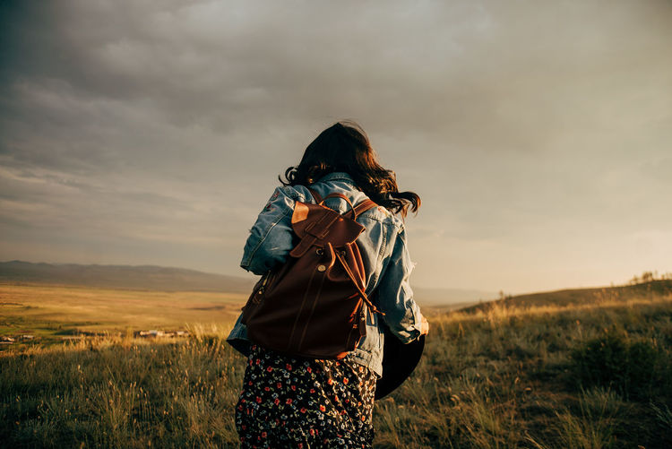 Rear view of woman with backpack walking on grass against sky