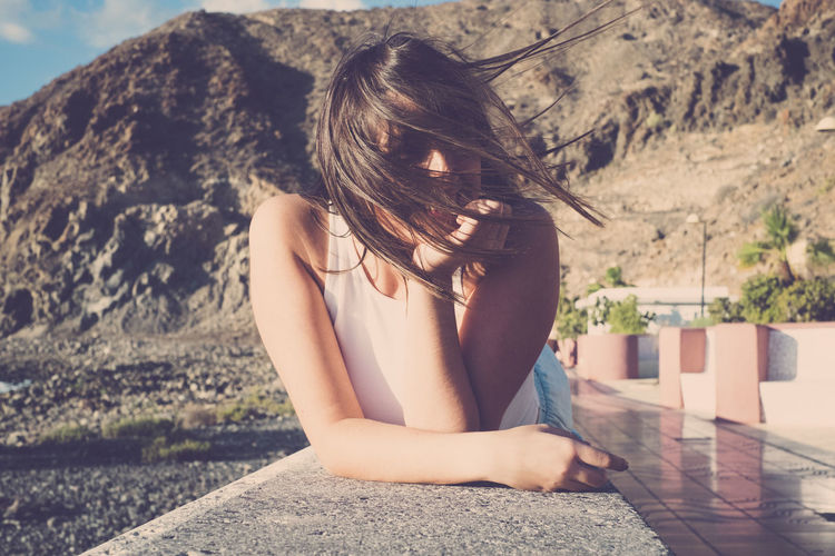 Young Woman With Tousled Hair Leaning On Retaining Wall Against Mountain