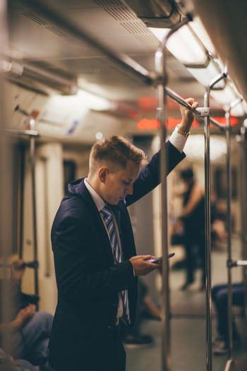 Businessman Using Mobile Phone While Traveling In Train